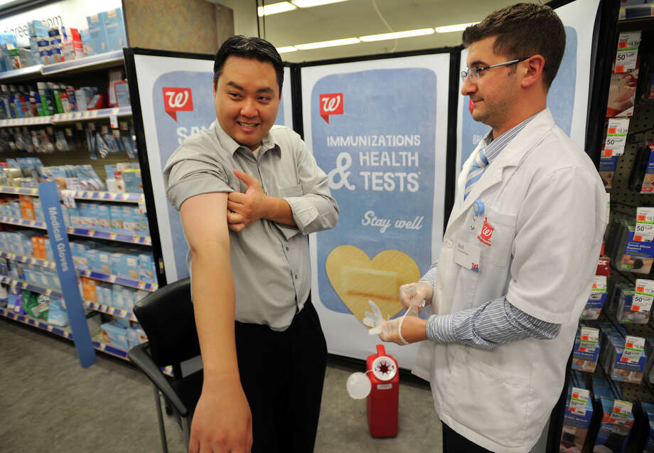 Walgreens employee Anthony Ngo, left, of Bridgeport, prepares to receive the 2014/15 flu vaccine from Pharmacy Manager Nick Riviere at Walgreens Pharmacy on Barnum Avenue in Stratford, Conn. on Monday, September 22, 2014. Photo: Brian A. Pounds / Connecticut Post