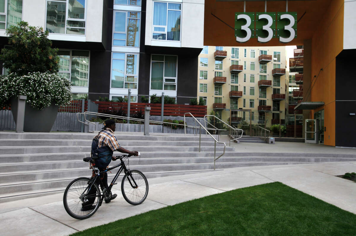 Clarence Cook walks his bike up to the office at 333 Harrison to apply for housing at the renovated former Stanford Hotel.