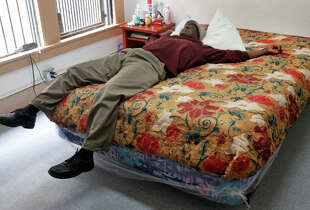 Cook, shown at a temporary residence, is applying for a unit at the newly made-over residence for homeless vets. lays on his bed after getting off the phone in his room at the Fairfax Hotel, where he is temporarily living Sept. 19, 2014 in San Francisco, Calif. Cook, who is an Army veteran, was homeless and in and out of prison for 30 years. He recently got his first private room with the transitional housing program Safe Haven and is currently applying for a room at the renovated former Stanford Hotel. The city is preparing to lease the building, which will house over 100 homeless veterans.