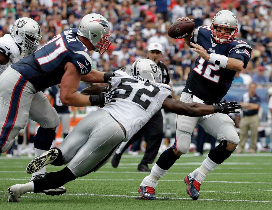 Raiders outside linebacker Khalil Mack reaches for Patriots quarterback Tom Brady during Sunday's game. The Oakland rookie had seven tackles. Photo: Steven Senne, STF / Associated Press / AP