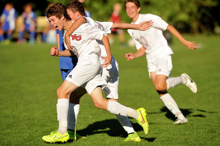 New Canaan's Alex Smith celebrates with his team after scoring the Rams' second goal during their soccer game against Darien at Conner Field in New Canaan, Conn., on Monday, Sep. 22, 2014. New Canaan won, 2-0. Photo: Jason Rearick / Stamford Advocate