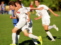 New Canaan's Alex Smith celebrates with his team after scoring the Rams' second goal during their soccer game against Darien at Conner Field in New Canaan, Conn., on Monday, Sep. 22, 2014. New Canaan won, 2-0.