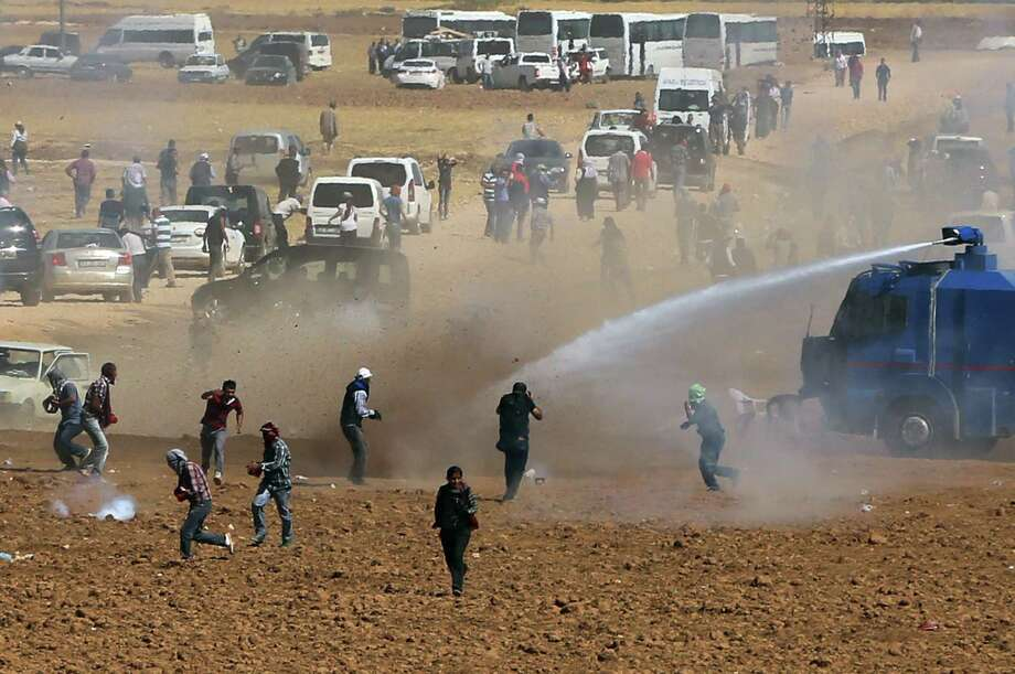 Riot police use water cannons to disperse Kurdish demonstrators who were clashing with Turkish security forces, as thousands of Syrian refugees continue to arrive at the border in Suruc, Turkey, Monday, Sept. 22, 2014. Turkey opened its border Saturday to allow in up to 60,000 people who massed on the Turkey-Syria border, fleeing the Islamic militants' advance on Kobani.(AP Photo/Burhan Ozbilici)  ORG XMIT: XBO108 Photo: Burhan Ozbilici / STR