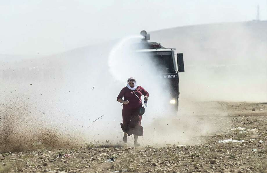 A Kurdish woman runs away from a water cannon near the Syrian border after Turkish authorities temporarily closed the border Monday at the southeastern town of Suruc in Sanliurfa province. Photo: BULENT KILIC, Staff / AFP