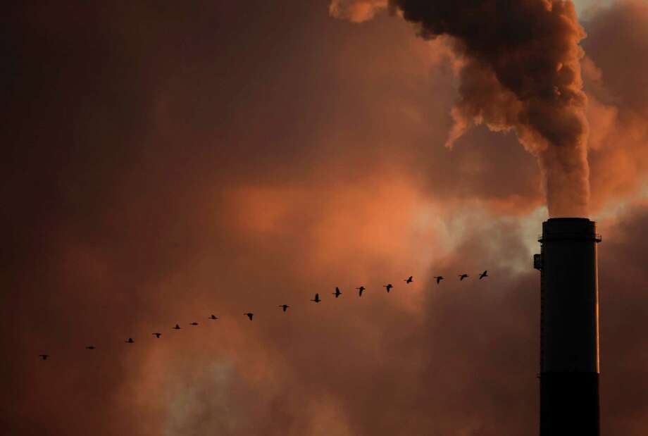 FILE - In this Saturday, Jan. 10, 2009, file photo, a flock of geese fly past a smokestack at the Jeffery Energy Center coal power plant near Emmitt, Kan. Hundreds of corporations, insurance companies and pension funds are calling on world leaders gathering for a U.N. summit on climate change this week to attack the problem by making it more costly for businesses to pollute. (AP Photo/Charlie Riedel, File) ORG XMIT: NYBZ102 Photo: Charlie Riedel / AP
