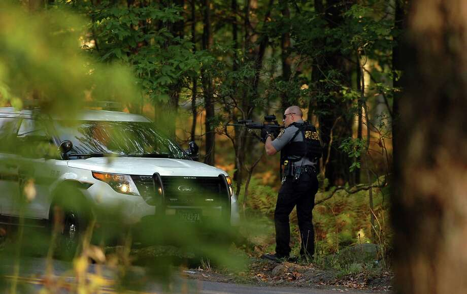 A Pennsylvania state trooper draws his weapon in a wooded area on Snow Hill Road in Price Township, Pa., during a huge manhunt for suspected killer Eric Frein on Sunday, Authorities have had no confirmed sightings of Frein. Photo: Butch Comegys, MBO / Scranton Times & Tribune