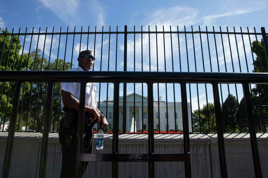 "A Secret Service police officer stands outside the White House in Washington, Monday, Sept. 22, 2014. Earlier, President Barack Obama said the Secret Service does ""a great job."" He says he is grateful for the ""sacrifices"" the service performs on his behalf and on behalf of his family. Obama made his comments Monday in the aftermath of Friday's security breach, when an intruder managed to jump the north fence of the White House and escape capture until he was inside the North Portico entrance of the presidential mansion. (AP Photo/Evan Vucci) ORG XMIT: DCEV201 Photo: Evan Vucci / AP"