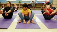 "Crockett Elementary health and wellness instructor Morgan Camp, left, leads a pose with students Darait Rodriguez, center, and Angel Benito. Student Julia Franco, 8, called yoga ""the best class."""