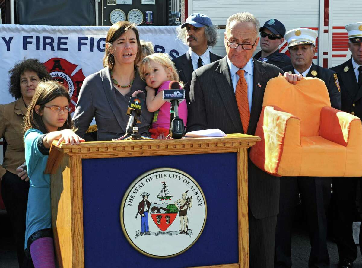 Bobbi Chase Wilding of Cobleskill along with her daughters Amanda, 9, and Maddie, 4, support U.S. Senator Charles Schumer, right, as he announces his push for new legislation that will ban the top ten noxious flame retardants from upholstered furniture and childrenOs products during a press conference at Firehouse of Engine 10/Ladder 3 on Monday, Sept. 22, 2014 in Albany, N.Y. Shumer is holding a piece of children's furniture that contains dangerous chemicals. (Lori Van Buren / Times Union)
