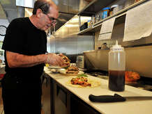Owner Tony Gencarelli makes a sandwich for the late-lunch crowd at The Village Table restaurant in the Springdale section of Stamford, Conn., on Monday, Sept. 22, 2014. The Village Table opened three weeks ago where Kim's Kitchen used to be in the Springdale Shopping Center and offers breakfast and lunch and is open late on select days for dinner.