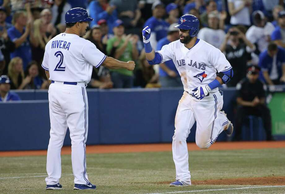 TORONTO, CANADA - SEPTEMBER 22: Jose Bautista #19 of the Toronto Blue Jays is congratulated by third base coach Luis Rivera #2 after hitting a solo home run in the fifth inning during MLB game action against the Seattle Mariners on September 22, 2014 at Rogers Centre in Toronto, Ontario, Canada. (Photo by Tom Szczerbowski/Getty Images) Photo: Tom Szczerbowski, Stringer / 2014 Getty Images