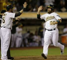 Oakland Athletics' Derek Norris, right, and Jonny Gomes (15) celebrate after scoring against the Los Angeles Angels in the first inning of a baseball game Monday, Sept. 22, 2014, in Oakland, Calif. Both scored on a single by Oakland's Geovany Soto. (AP Photo/Ben Margot)