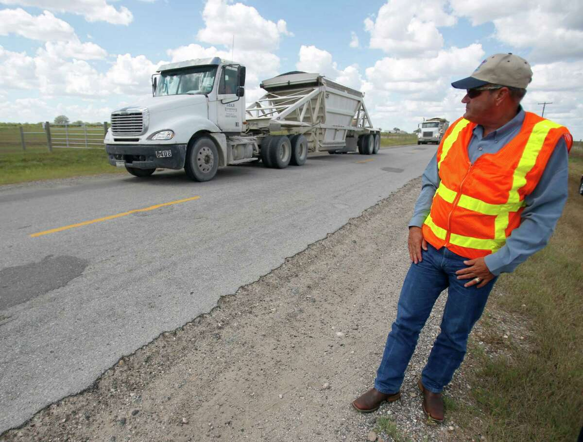 Texas Department of Transportation Executive Director retired Lt. Gen. Joe Weber watches trucks as he examines a county road in Karnes County Thursday afternoon Sept. 11, 2014 in the Eagle Ford shale area after testifying earlier in the day at a House Energy Resource committee meeting in Cuero.
