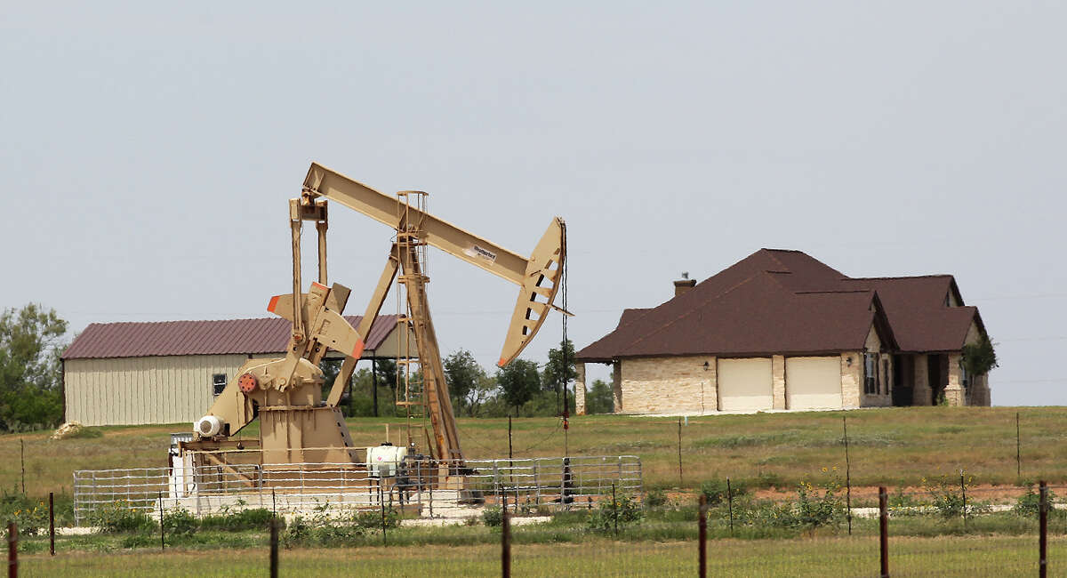 A pump jack sits near a house along County Road 541 near Kosciusko, Texas, Tuesday, July 15, 2014.