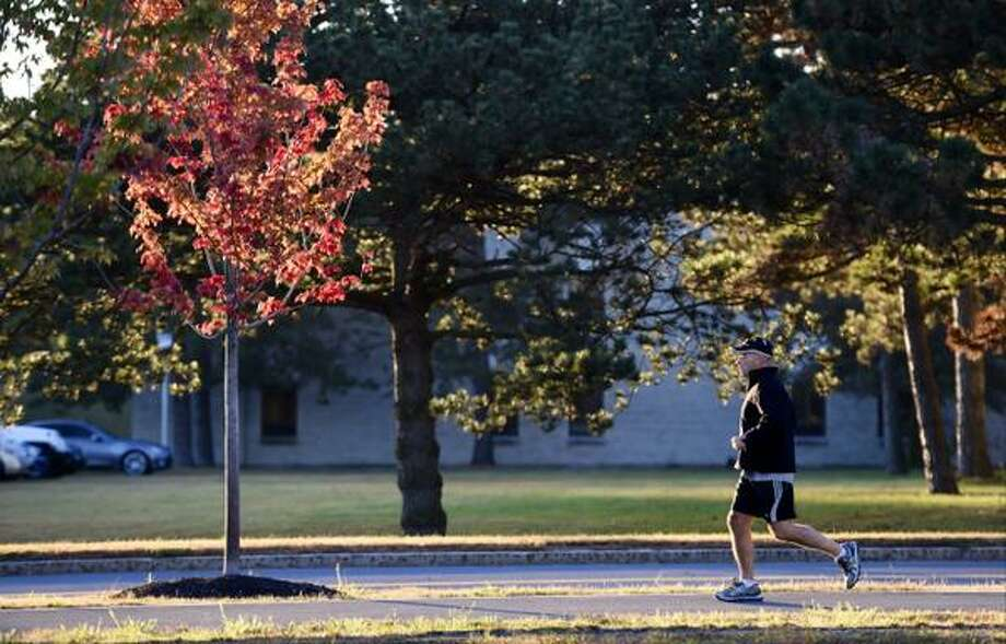 On the first full day of fall, a jogger -- State Police Lt. Tony Oliver -- turns by a brightly colored tree on the University at Albany campus. (Skip Dickstein / Times Union)