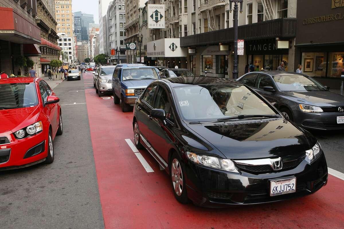 "A black sedan bearing the distinctive ""U"" logo of the Uber ridesharing service takes the transit lane on Geary Street in San Francisco on Friday, September 19, 2014."