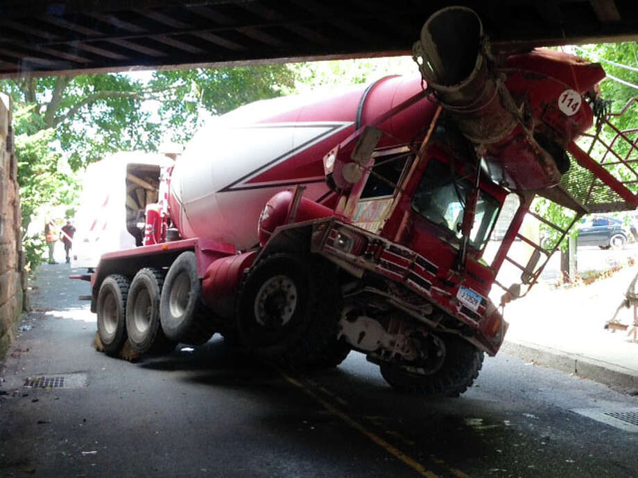 This cement mixer became wedged under the railroad overpass above Mill Plain Road at midday Monday, shutting down traffic at the busy intersection with the Post Road for more than an hour while it was removed. Photo: Fairfield Fire Department / Fairfield Citizen
