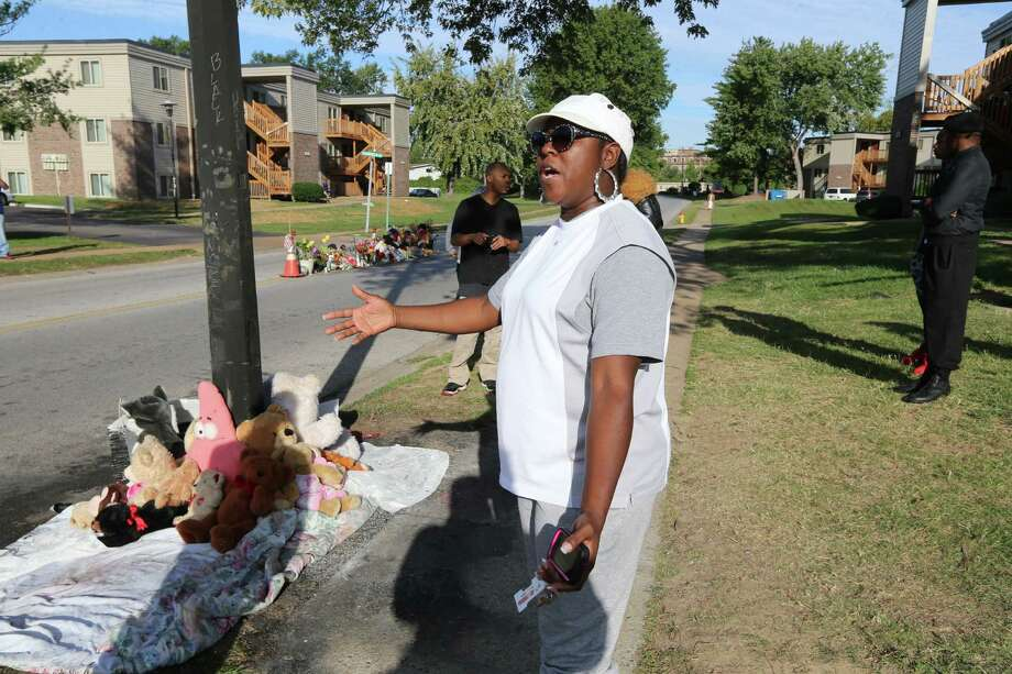 A woman gestures by a new teddy bear memorial on Tuesday, Sept. 23, 2014, in Ferguson, Mo., near the spot of where Michael Brown was shot by Ferguson police office Darren Wilson on Aug. 9.  The original teddy bear memorial was destroyed by fire earlier Tuesday morning. Ferguson police spokesman Devin James says the cause of the fire is under investigation.   EDWARDSVILLE INTELLIGENCER OUT; THE ALTON TELEGRAPH OUT Photo: David Carson, AP / St. Louis Post-Dispatch