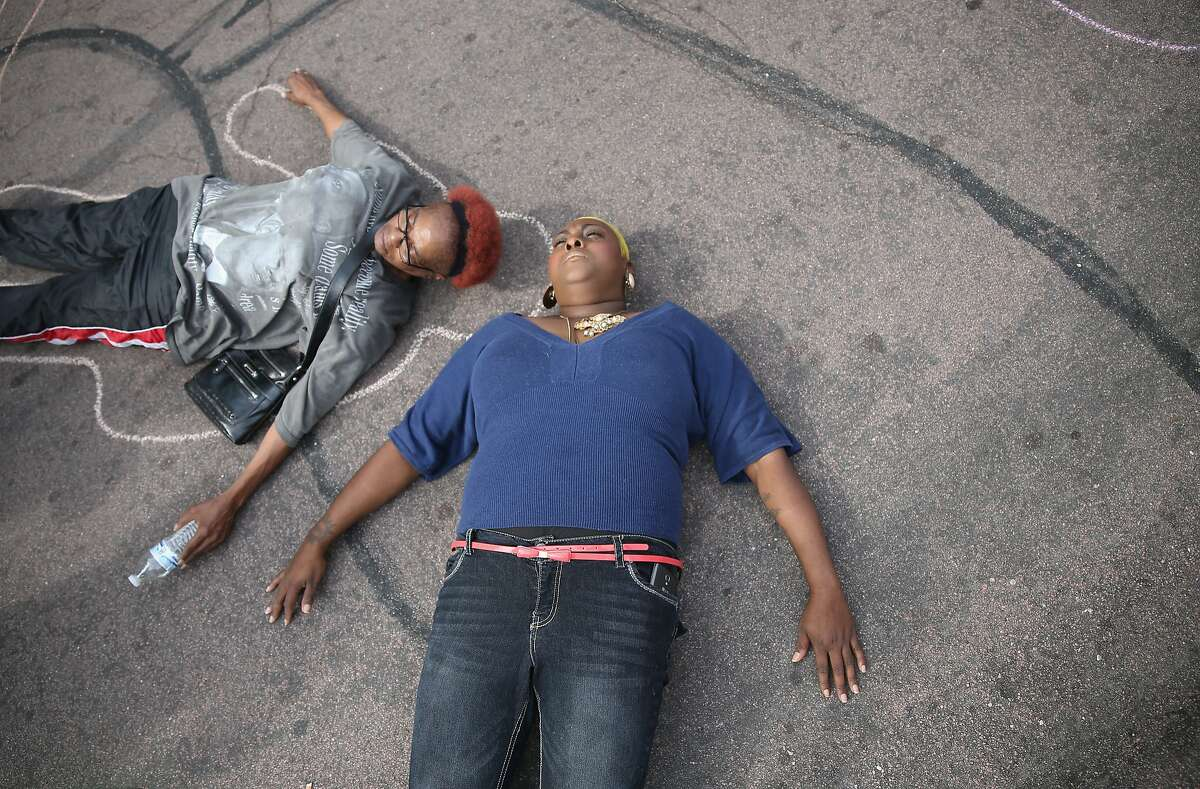 Protesters lay on the ground to draw lines around their bodies as they and other demonstrators protest outside of the Buzz Westfall Justice Center where a grand jury will begin looking at the circumstances surrounding the fatal police shooting of an unarmed teenager Michael Brown on August 20, 2014 in Clayton, Missouri. Brown was shot and killed by a Ferguson, Missouri police officer on August 9. Despite the Brown family's continued call for peaceful demonstrations, violent protests have erupted nearly every night in Ferguson since his death