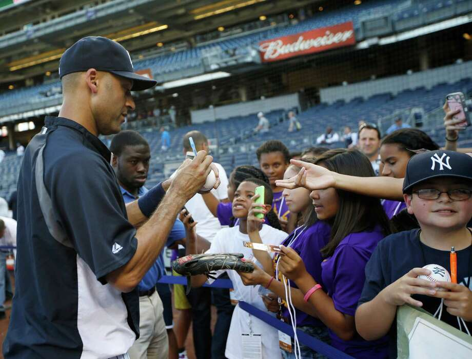 Fans surround New York Yankees player Derek Jeter for his autograph at Yankee Stadium in September. Photo: Kathy Willens, STF / AP