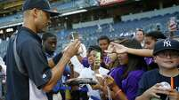 Fans surround New York Yankees player Derek Jeter for his autograph at Yankee Stadium in September.