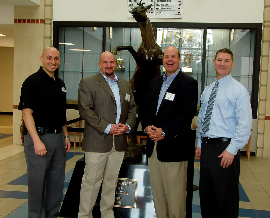 Kingwood High School Assistant Principal Michael Nasra, left, and Kingwood High School Principal Ted Landry, right  greet guest principals Jason Core and Steve Hefner during a tour of the school. Photo: Hisd