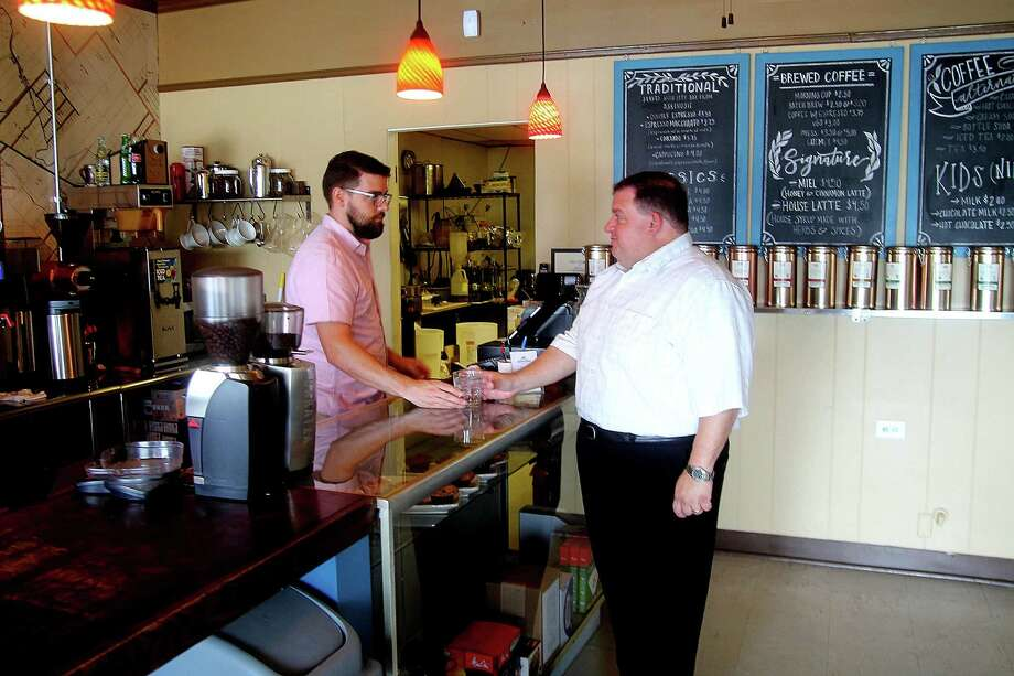 """Pearland Coffee Roasters co-owner Jeremy Perrine serves customer Tony Quarto at the coffee shop, 4106 Broadway. """"I've seen the growth (in Pearland) everyone is talking about, even having lived here only a few years,"""" Perrine says. Photo: Pin Lim, Freelance / Copyright Pin Lim."""