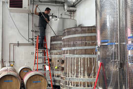 Winemaker Chris Brockway pitchforks Arrowhead Zinfandel in a barrel at his winery, Broc Cellars in Berkeley. .