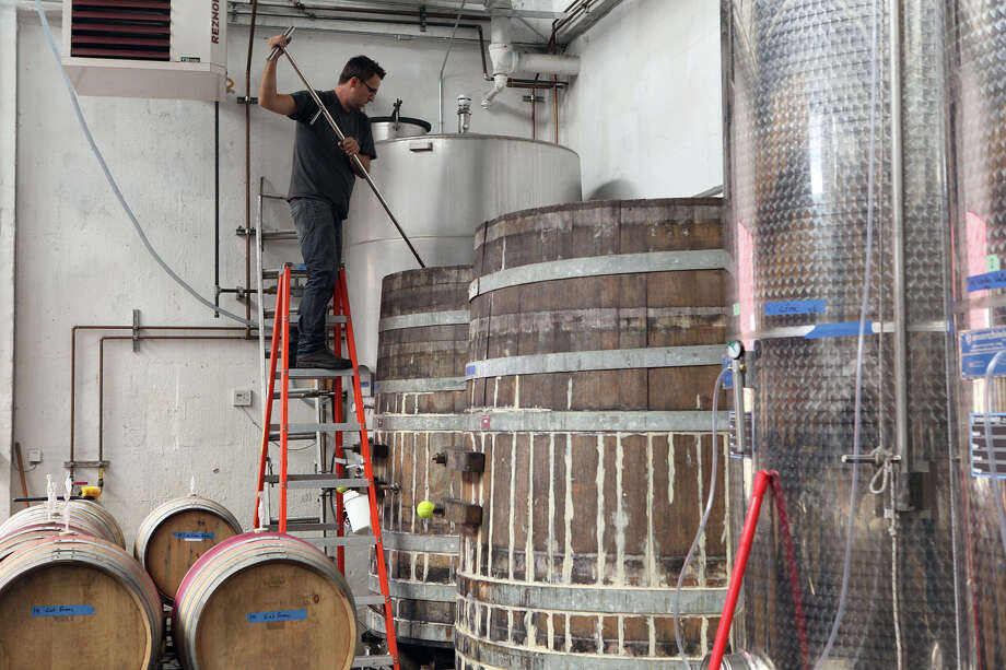 Winemaker Chris Brockway pitchforks Arrowhead Zinfandel in a barrel at his winery, Broc Cellars in Berkeley. . Photo: Liz Hafalia, Staff / The Chronicle / ONLINE_YES