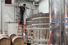 Winemaker Chris Brockway pitchforks Arrowhead Zinfandel in a barrel at his winery, Broc Cellars in Berkeley. .