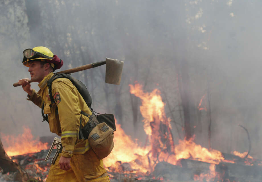 A firefighter from the Tuolumne-Calaveras County Fire Department walks along a containment line during a controlled burn. Photo: Marcio Jose Sanchez, STF / Associated Press / AP