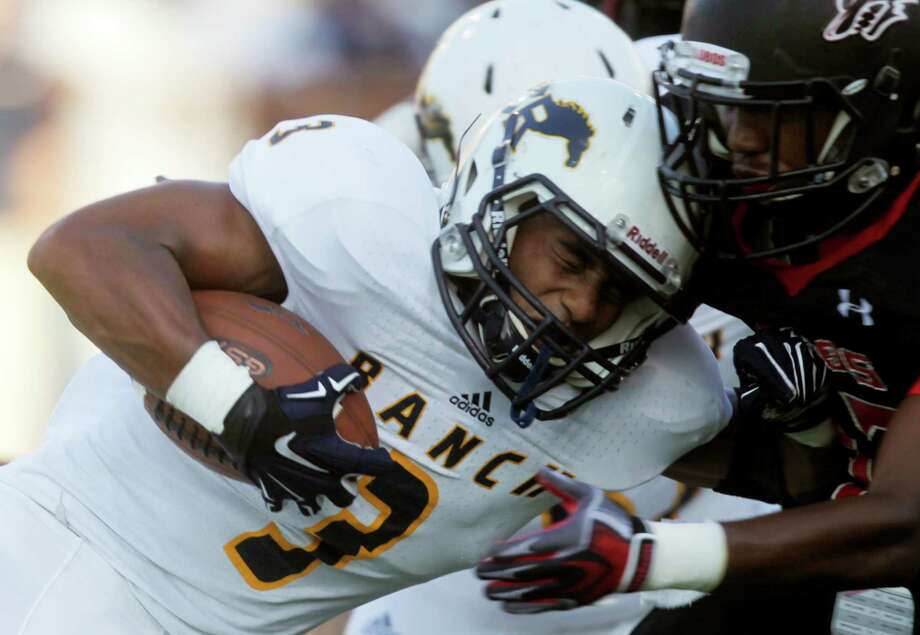 Cypress Ranch running back Joseph Johnson is hit by Langham Creek's Rashad Gould during the first half of a high school football game at the Berry Center on Saturday, Sept. 20, 2014, in Cypress. ( J. Patric Schneider / For the Chronicle ) Photo: J. Patric Schneider, Freelance / © 2014 Houston Chronicle
