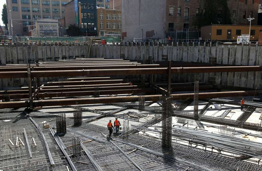 Construction workers walk across a network of rebar on the second level of the Transbay Transit Center project in San Francisco, Calif. on Tuesday, Sept. 23, 2014. Photo: Paul Chinn, The Chronicle