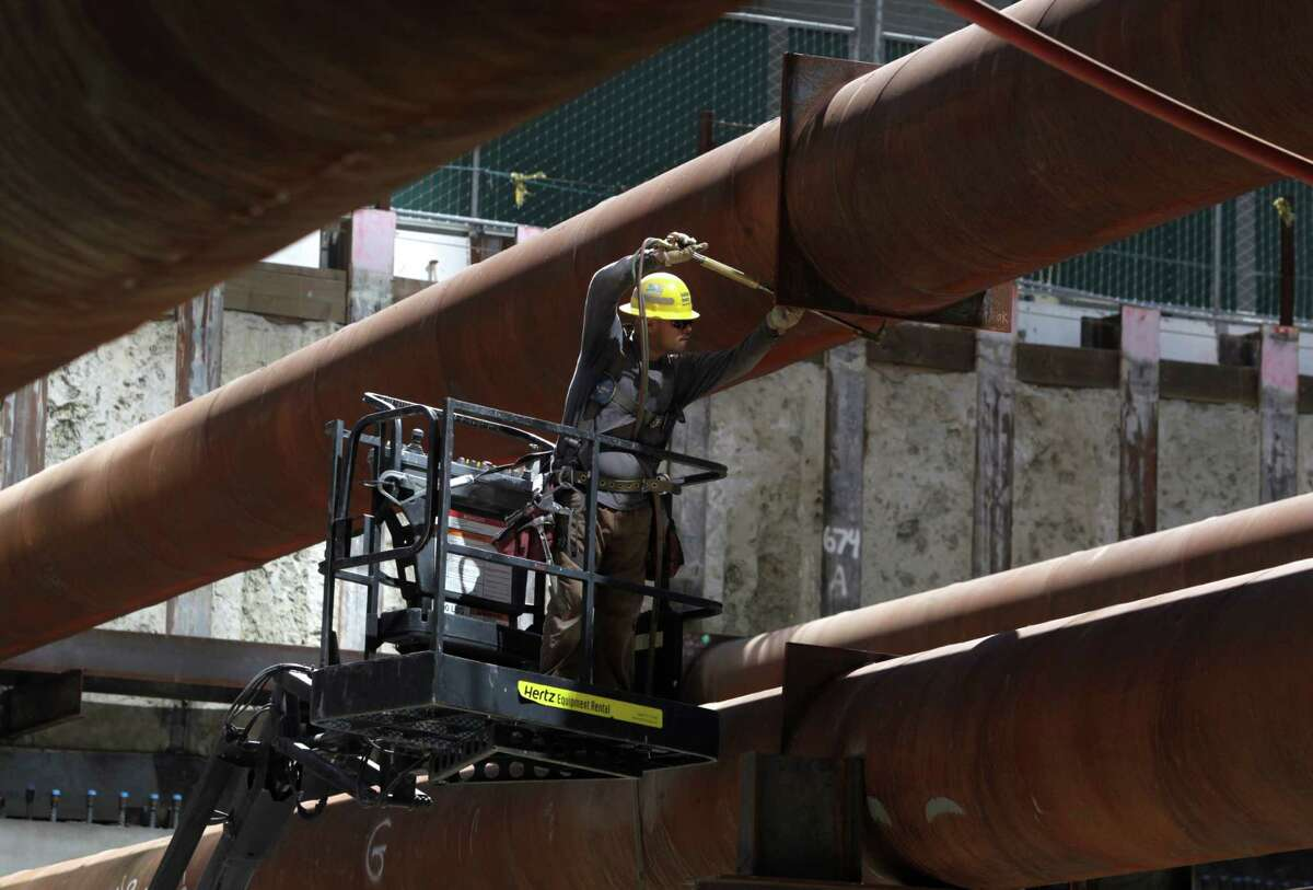 A construction worker uses a blow torch to cut steel braces on the Transbay Transit Center project in San Francisco.