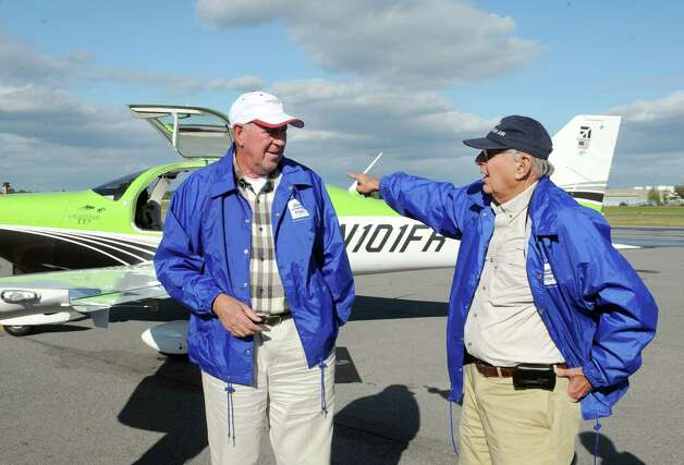 Pilots Field Morey, left, and Conrad Teitell talk about their cross country flight to visit 49 United State Capitals after landing at Albany International Airport on Tuesday, Sept. 23, 2014, in Colonie, N.Y. The Albany landing was the 28th State Capital visited by the two.  (Michael P. Farrell/Times Union) Photo: Michael P. Farrell / 00028722A