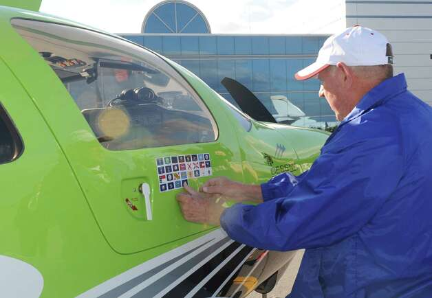 Pilot Field Morey attaches a New York State flag sticker to his plane after landing on his cross country flight to visit 49 United State Capitals at Albany International Airport on Tuesday Sept. 23, 2014 in Colonie, N.Y. The Albany landing was the 28th State Capital visited by Morey and Conrad Teitell.  (Michael P. Farrell/Times Union) Photo: Michael P. Farrell / 00028722A
