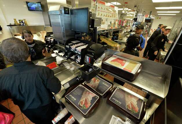 Workers prepare food in the production area of the McDonald's restaurant at Crossgates Commons Tuesday morning, Sept. 23, 2014, in Albany, N.Y.        (Skip Dickstein/Times Union) Photo: SKIP DICKSTEIN / 00028719A