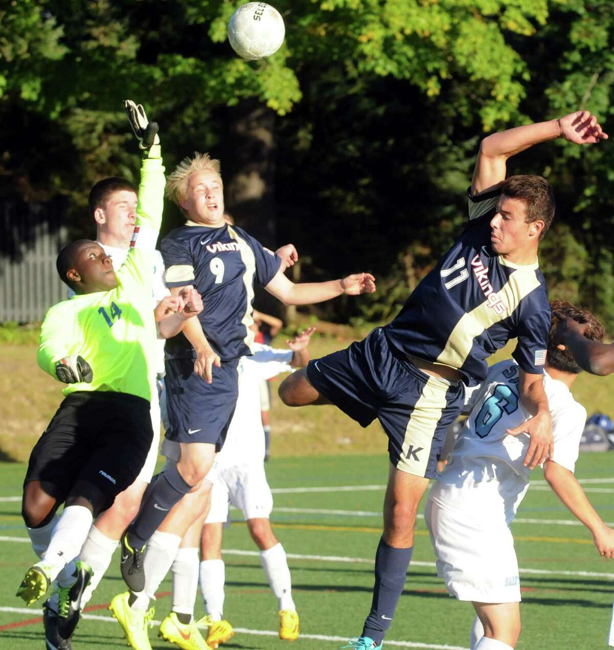 King's Alex Currie, center, and Jack Rozen collide with the Canterbury goalie Alec Astorga as King hosts Canterbury in Stamford, Conn., Sept. 23, 2014.