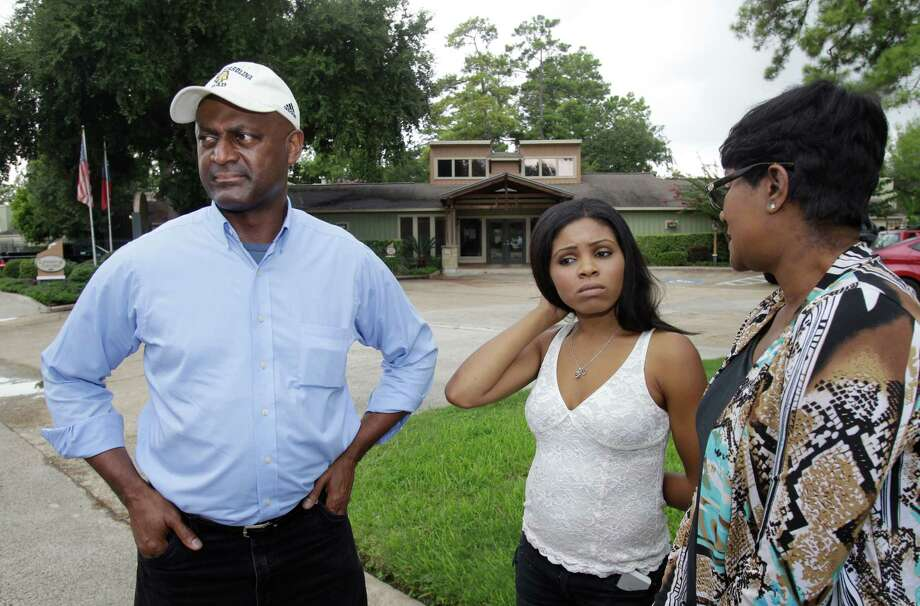 Shaniqua Clark is flanked last week by her uncle and aunt, Gary and Valencia Goodridge, while visiting the site where Clark's father was killed July 9. Photo: Melissa Phillip, Staff / © 2014  Houston Chronicle