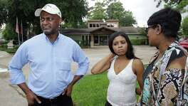 Shaniqua Clark is flanked last week by her uncle and aunt, Gary and Valencia Goodridge, while visiting the site where Clark's father was killed July 9.