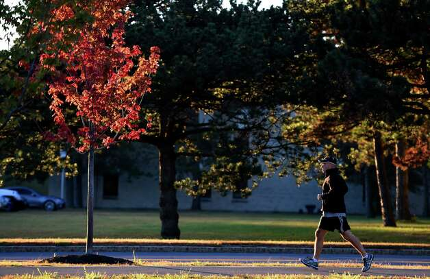 On the first full day of fall, a jogger -- State Police Lt. Tony Oliver -- turns by a brightly colored tree on the University at Albany campus. (Skip Dickstein / Times Union) Photo: SKIP DICKSTEIN / 00028719A