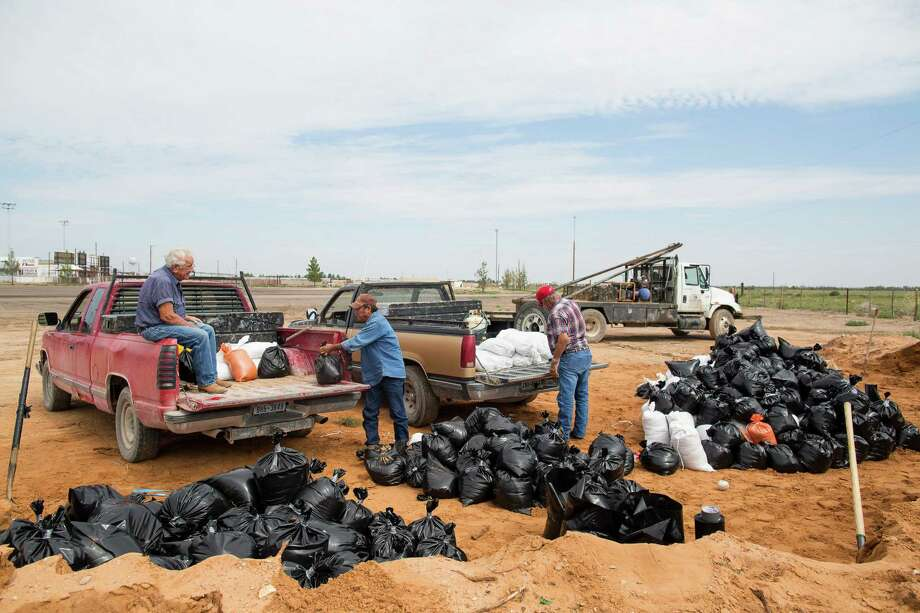 Pecos, Texas, residents load pickup trucks with sandbags Tuesday, Sept. 23, 2014, in anticipation of the Pecos River overflowing after days of heavy rainfall in New Mexico.    (AP Photo/Odessa American, Courtney Sacco) Photo: Courtney Sacco, MBR / Odessa American