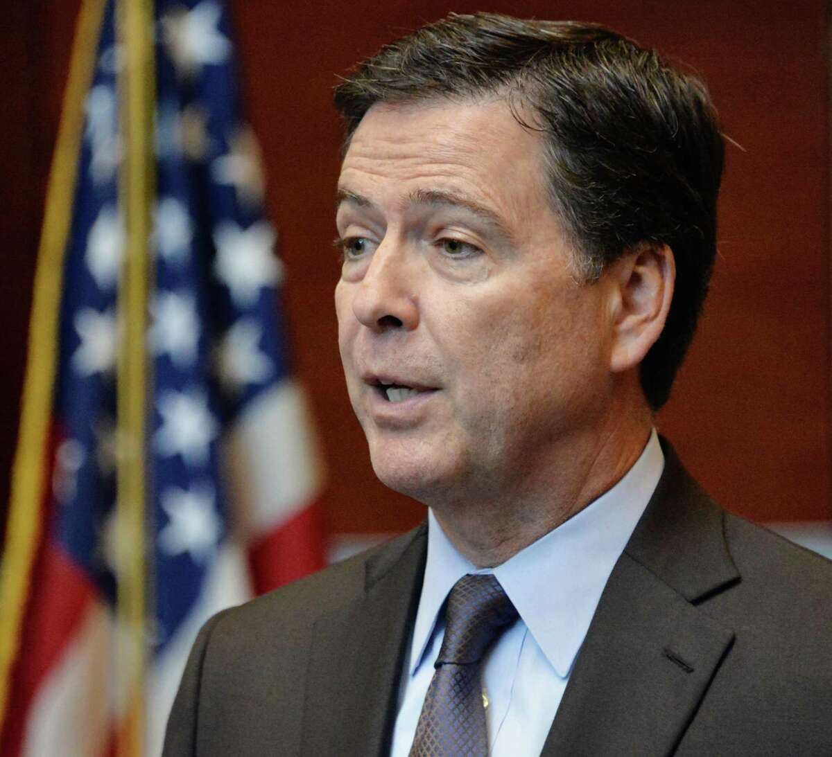 FBI Director James B. Comey, center, at podium, the presidentially appointed seventh Director of the FBI, is joined by Albany area local, state and federal law enforcement agency partners during a news conference Tuesday Sept. 23, 2014, in Albany, NY. (John Carl D'Annibale / Times Union)