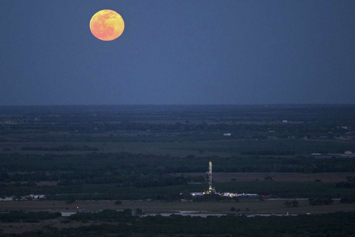 The full moon rises above an oil drilling rig Wednesday, May 14, 2014 in an aerial image taken near Karnes City, Texas.