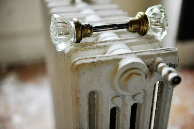 A door knob is seen on top of a radiator, two items that will be salvaged by workers with Historic Albany Foundation at a home on Morris St. on Tuesday, Sept. 16, 2014, in Albany, N.Y.     (Paul Buckowski / Times Union) Photo: Paul Buckowski / 00028128A