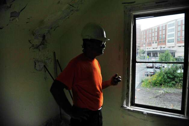 The Albany Medical Center is seen through the window of 148 Morris St. as Peter Leue, a salvage expert for Historic Albany Foundation talks about the salvage work being done inside the home on Tuesday, Sept. 16, 2014, in Albany, N.Y.     (Paul Buckowski / Times Union) Photo: Paul Buckowski / 00028128A
