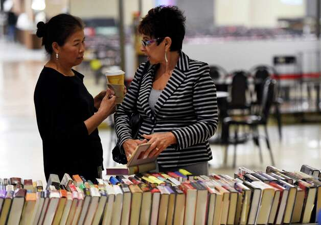 Chyongere Hsieh, left, and Diane Ray discuss a potential book purchase during a book sale that benefits victims with AIDS Tuesday morning, Sept. 23, 2014, on the Empire State Plaza Concourse in Albany, N.Y. The event runs through Friday 10 a.m.- 4 p.m. (Skip Dickstein/Times Union) Photo: SKIP DICKSTEIN / 00028709A