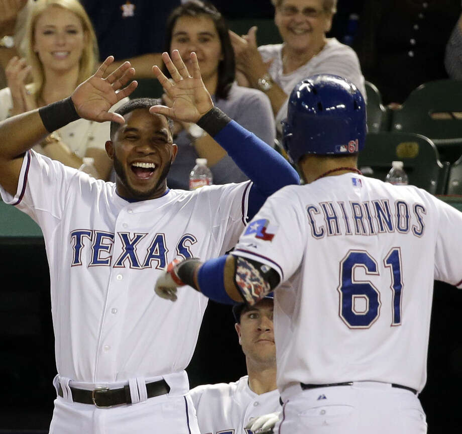 The Rangers' Elvis Andrus waits to greet Robinson Chirinos, who returned to the dugout after hitting a home run in the fourth inning in Arlington. Photo: Tony Gutierrez / Associated Press / AP
