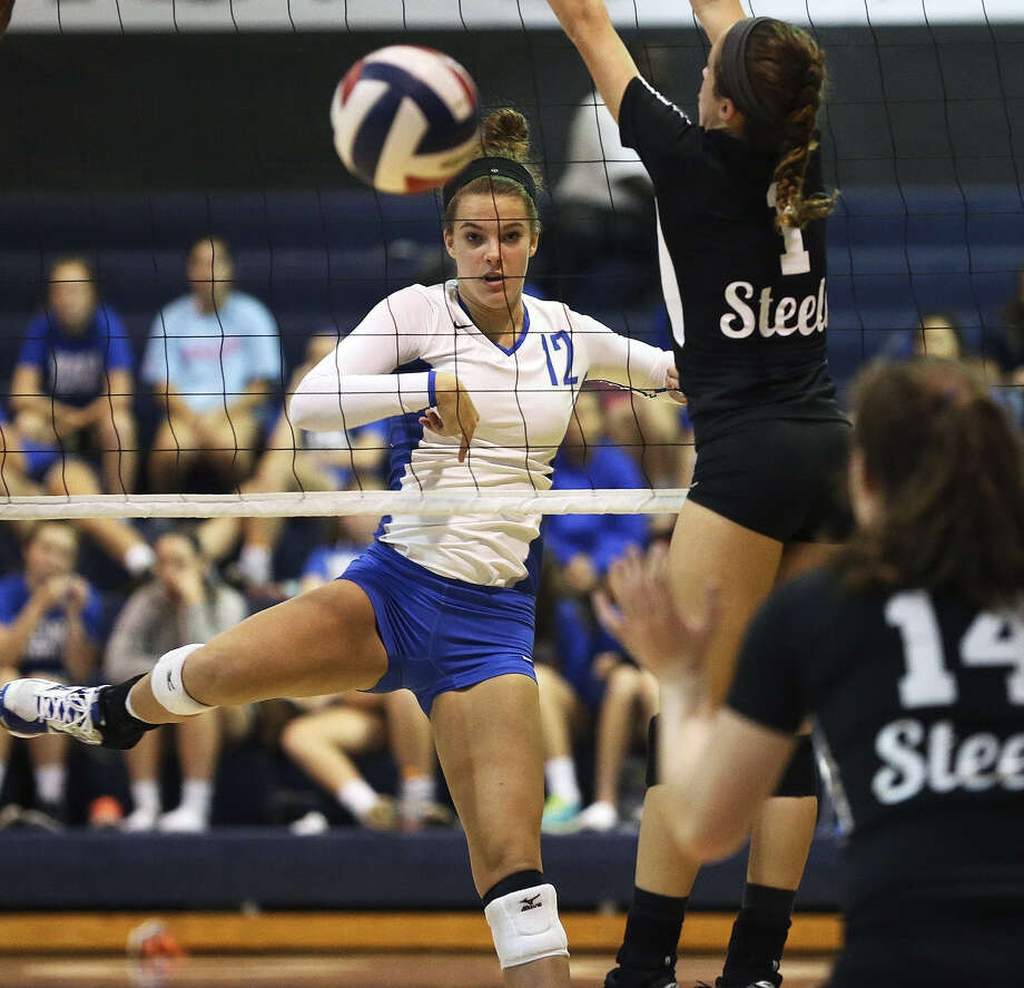 New Braunfels' Faith Heller (12) follows through on a spike as Steele defends in the Unicorns' 22-25, 25-18, 27-25, 25-21 win. Photo: Tom Reel / San Antonio Express-News