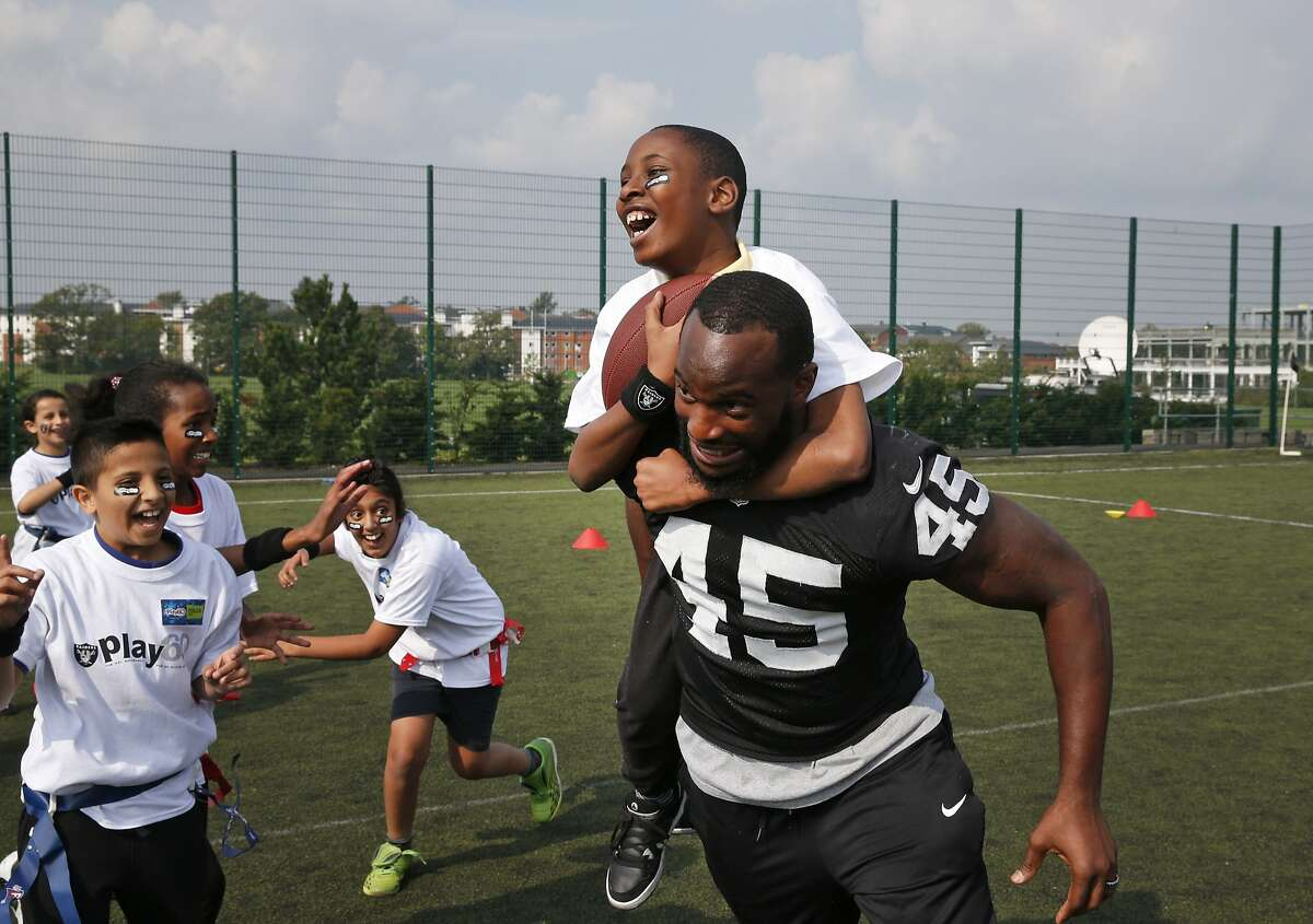 Oakland Raiders Marcel Reece plays football with children during an event in September 2014.